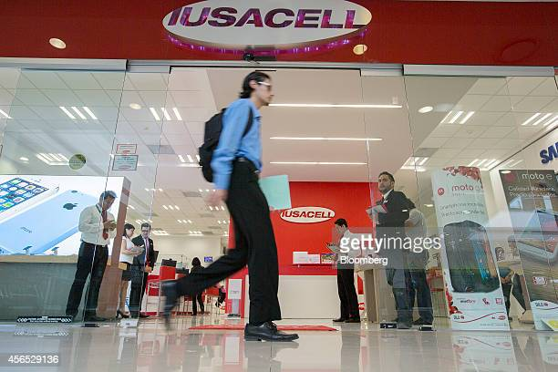 A man walks past a Grupo Iusacell SA customer service center at the Buenavista Mall in Mexico City Mexico on Wednesday Oct 1 2014 Japanese...
