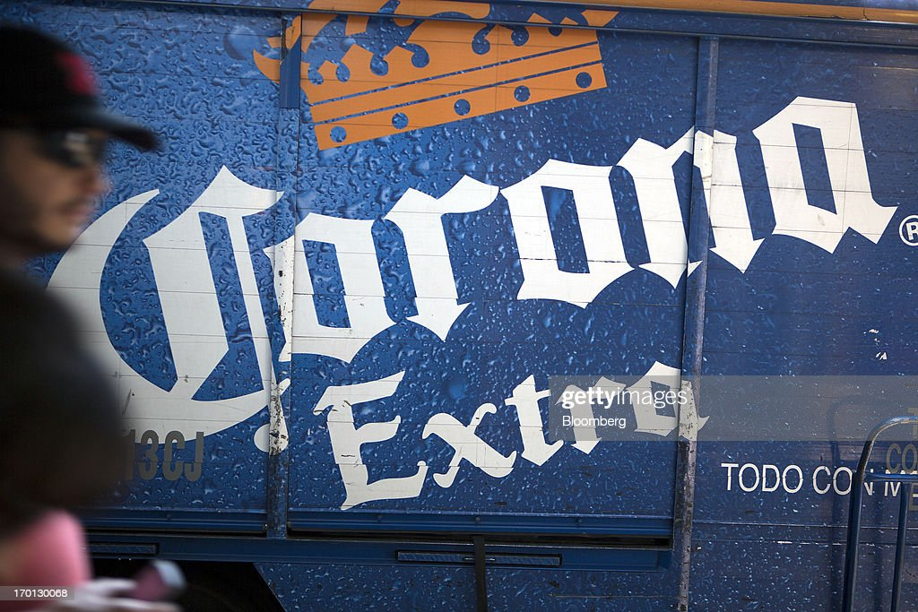 A man walks past a Grupo Modelo SAB delivery truck with then logo for their Corona beer in Mexico City, Mexico, on Thursday, June 6, 2013. Heineken NV and Grupo Modelo SAB, the dominant brewers in Mexico with brands such as Dos Equis and Corona, are nearing the end of an almost three-year-old government antitrust probe. Photographer: Susana Gonzalez/Bloomberg via Getty Images