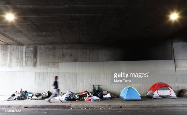 A man walks past a homeless encampment beneath an overpass on June 5 2019 in Los Angeles California The homeless population count in Los Angeles...