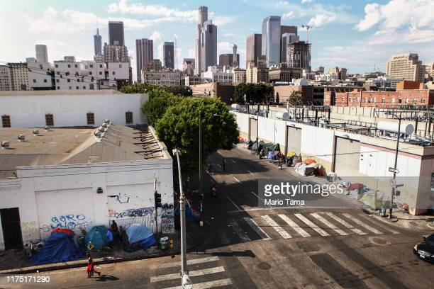A man walks past a homeless tent encampment in Skid Row on September 16 2019 in Los Angeles California Skid Row is home to thousands who either live...