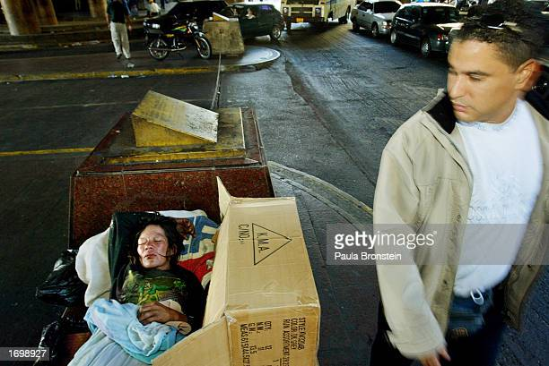 A man walks past a homeless women sleeping on the street December 22 2002 in Caracas Venezuela Approximately 80% of the people live in poverty in...
