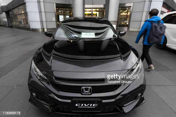 A man walks past a Honda Motor Co Civic Hatchback vehicle displayed outside the company's headquarters on February 19 2019 in Tokyo Japan Honda...