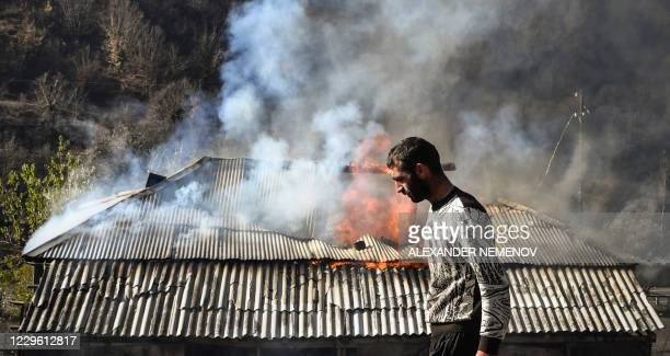 Man walks past a house burning in the village of Charektar outside the town of Kalbajar on November 14 during the military conflict between Armenia...