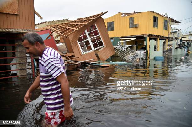 Man walks past a house laying in flood water in Catano town, in Juana Matos, Puerto Rico, on September 21, 2017. Puerto Rico braced for potentially...