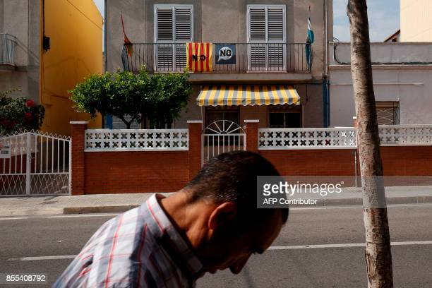 Man walks past a house where a Catalan flag and a banner calling to vote NO in the referendum on independence for October 1 hang in La Canonja, near...