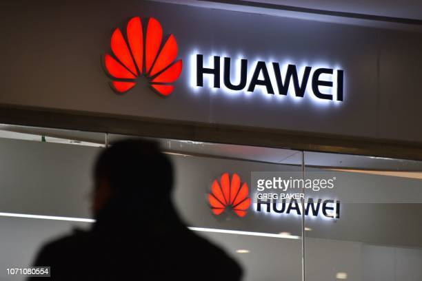 A man walks past a Huawei store in Beijing on December 10 2018 China on December 10 protested Canada's inhumane treatment of an executive of telecom...