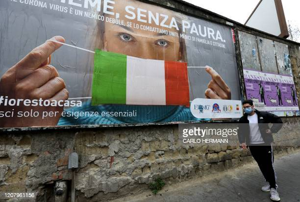 A man walks past a huge billboard that shows a woman with as protective mask in the colours of an Italian flag and which reads All together without...