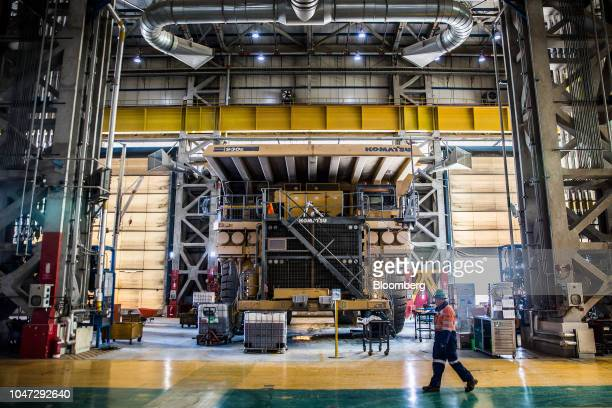 Man walks past a Komatsu Ltd. 930E dump truck in a maintenance shop at the Oyu Tolgoi copper-gold mine, jointly owned by Rio Tinto Group's Turquoise...