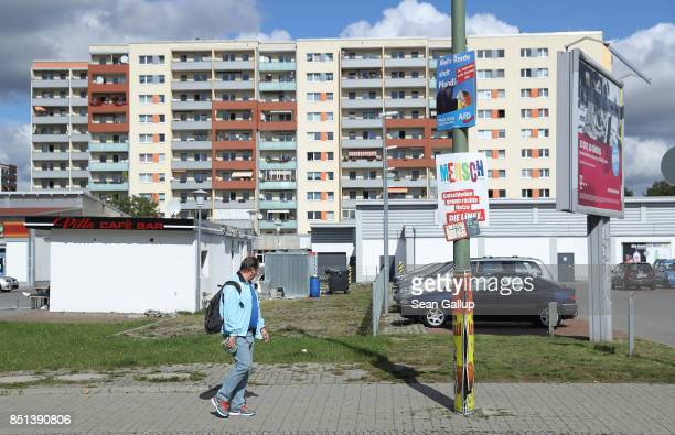 A man walks past a lamppost on which hang election campaign posters of the rightwing Alternative for Germany political party and the leftwing Die...