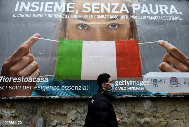 Man walks past a large billboard raising awareness to the measures taken by the Italian government to fight against the spread of the COVID-19 which...