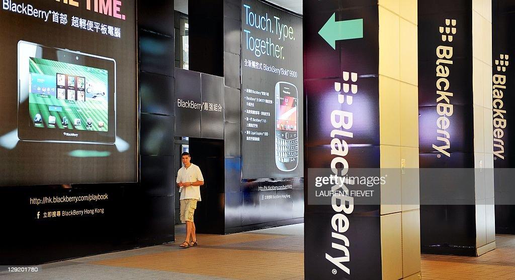A man walks past a large BlackBerry adve : News Photo