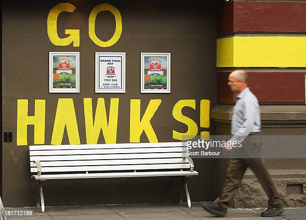 A man walks past a large 'Go Hawks' sign which is written on the wall of the Arcadia Hotel in South Yarra on September 24 2013 in Melbourne Australia...