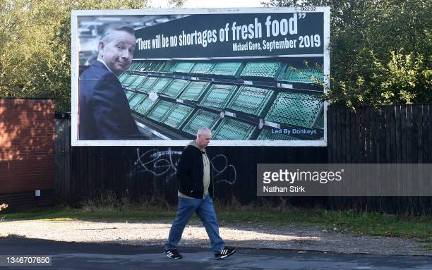 Man walks past a Led By Donkeys billboard displaying Micheal Gove quote saying 'There will be no shortages of fresh food' on October 15, 2021 in...
