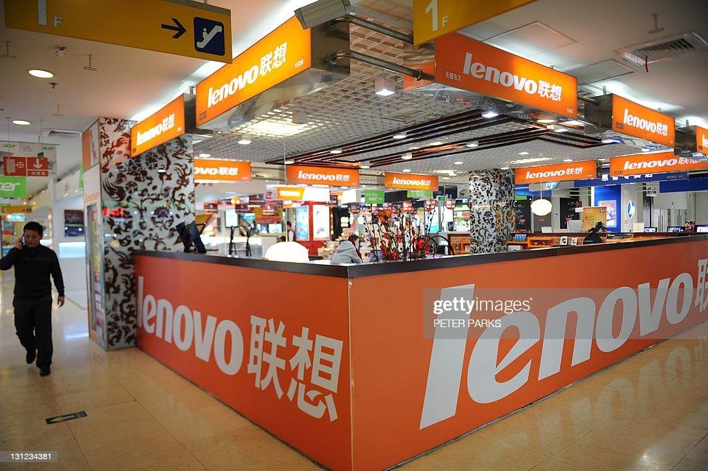 A man walks past a Lenovo shop in a comp : News Photo