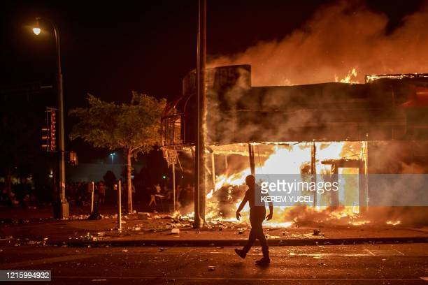 TOPSHOT A man walks past a liquor store in flames near the Third Police Precinct on May 28 2020 in Minneapolis Minnesota during a protest over the...