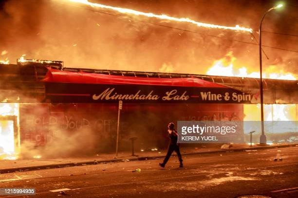 Man walks past a liquor store in flames near the Third Police Precinct on May 28, 2020 in Minneapolis, Minnesota, during a protest over the death of...