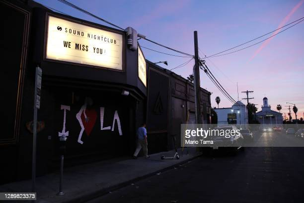 "Man walks past a long-shuttered nightclub with the message ""We Miss You"" in Hollywood amid the COVID-19 pandemic on December 6, 2020 in Los Angeles,..."