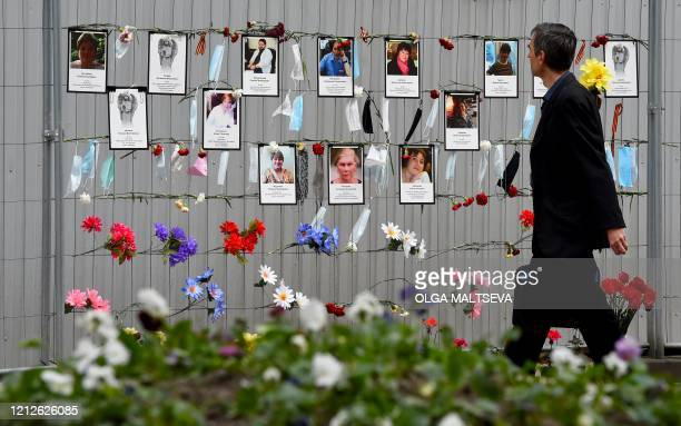 Man walks past a makeshift memorial for medical workers who died from the COVID-19 set up outside the local health department in Saint Petersburg on...