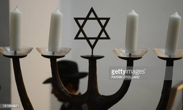 A man walks past a menorah during a ceremony to ordain four rabbis at the synagogue in Cologne western Germany on September 13 2012 The ordination of...