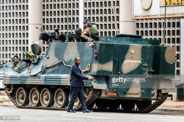 TOPSHOT A man walks past a military tank parked on the side of a street in the Zimbabwean capital Harare on November 16 a day after the military...