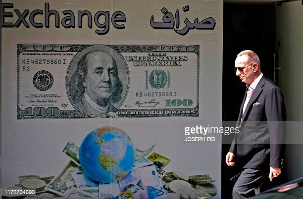 Man walks past a money exchange company in the Lebanese capital Beirut on October 1, 2019. - Lebanon's central bank announced Monday adopting a...