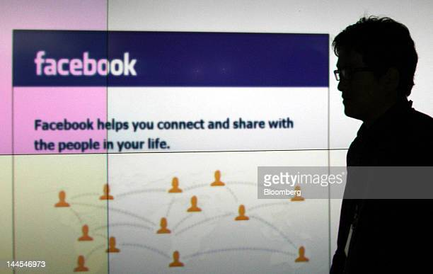 A man walks past a monitor displaying the Facebook Inc website in this arranged photograph in Tokyo Japan on Wednesday May 16 2012 Facebook Inc is...