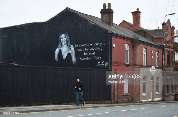 Man walks past a mural by Artists Scott Wilcock which pays tribute to TV star Caroline Flack on February 21, 2021 in Wigan, England. Ms Flack, best...