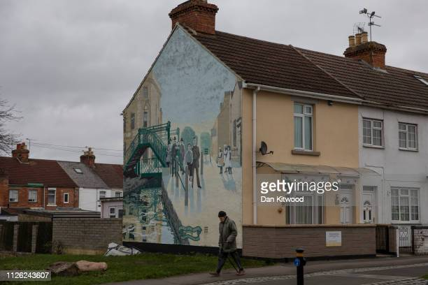 A man walks past a mural commemorating local poet Alfred Williams who died in 1930 near the town centre on February 20 2019 in Swindon England The...