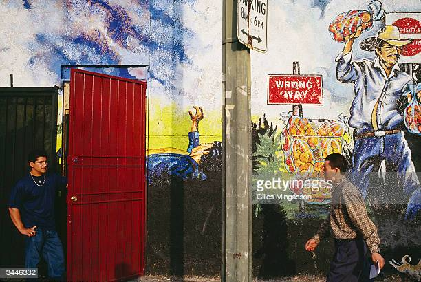 A man walks past a mural depicting the existence and dangers of immigration to the US in PicoUnion one of Los Angeles buslting immigrant...