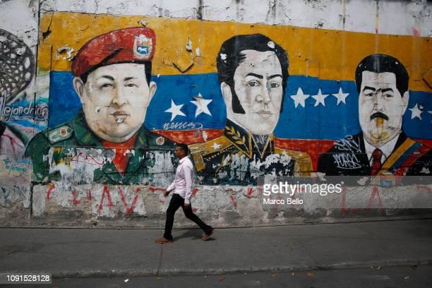 A man walks past a mural depicting Venezuela's late President Hugo Chávez Latin American independence hero Simon Bolivar and Venezuela's President...
