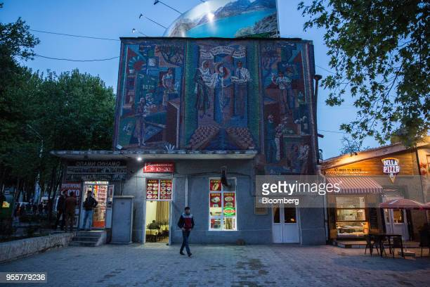 A man walks past a mural displayed on a building housing a fastfood restaurant in Dushanbe Tajikistan on Saturday April 21 2018 Flung into...
