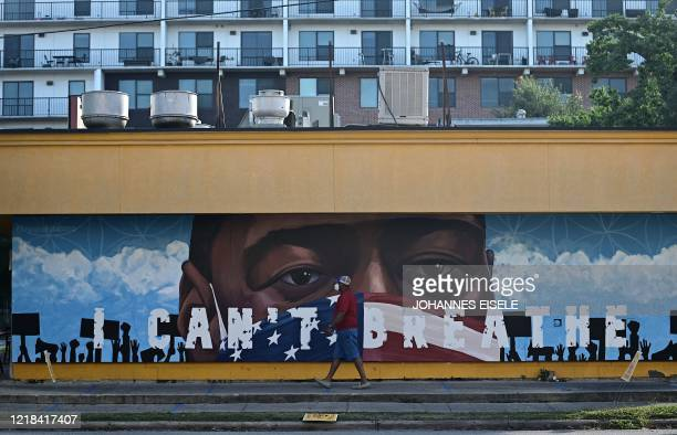 A man walks past a mural for George Floyd in Houston Texas on June 82020 Democrats vowed June 7 2020 to press legislation to fight systemic racism in...