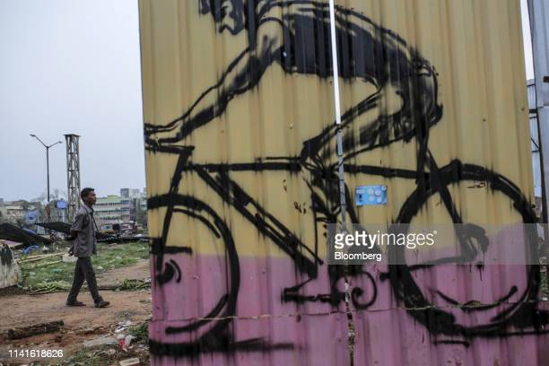 A man walks past a mural of a cyclist on metal hoarding panels after Cyclone Fani passes in Bhubaneshwar Odisha India on Sunday May 5 2019...