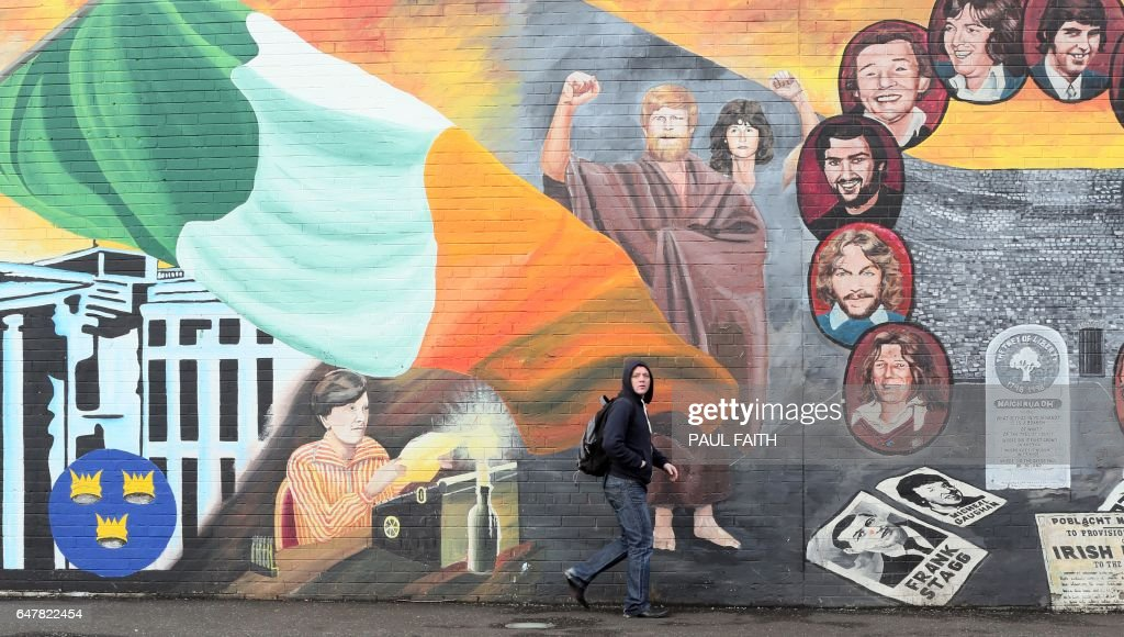 A man walks past a mural on the Catholic Falls Road in Belfast, Northern Ireland, on March 4, 2017. Northern Ireland's main political parties on March 4 were facing a three-week deadline to mend fences after snap elections aimed at sorting out the bad blood between them left them deadlocked. If the pro-British Democratic Unionist Party (DUP) and Sinn Fein, the Irish republican party, cannot agree to form a power-sharing executive -- a cornerstone of peace in Northern Ireland -- then governance of the British province could return to London. PHOTO / Paul FAITH