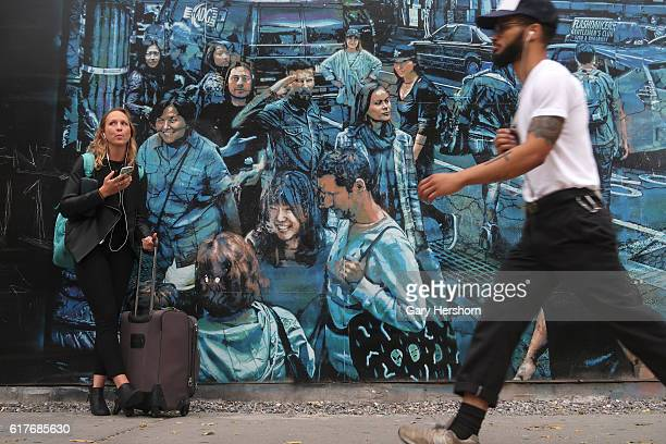 A man walks past a mural painted by artist Logan Hicks on the HoustonBowery Wall on October 20 2016 in New York City