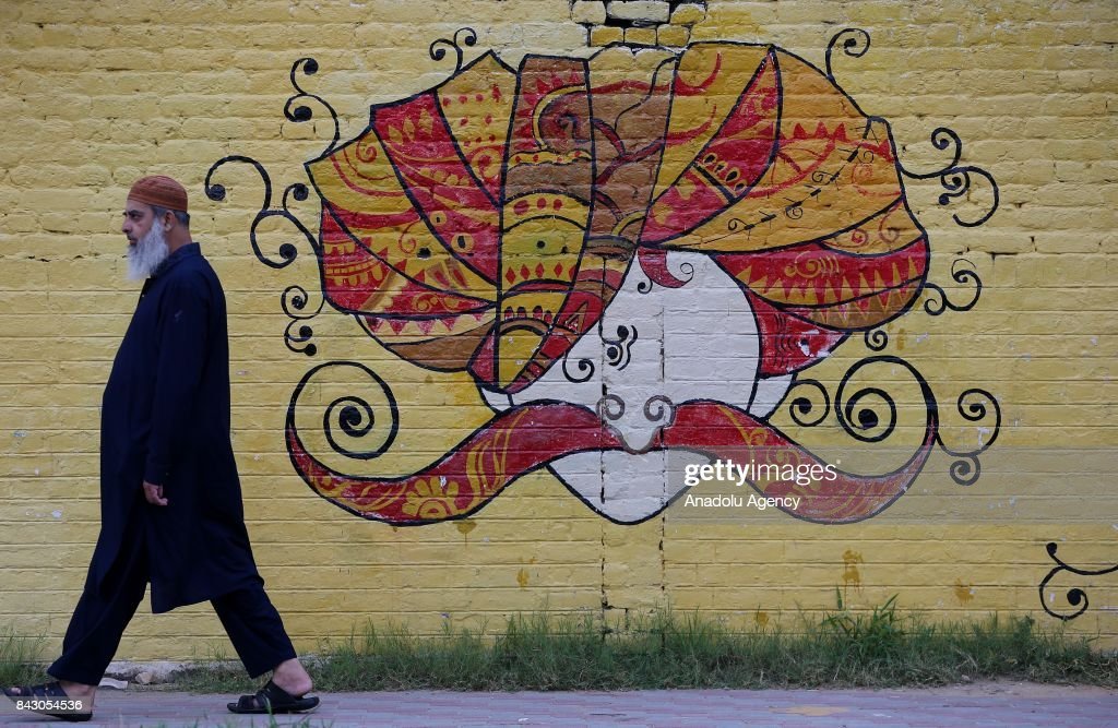 A Man Walks Past A Mural Painting On An Exterior Wall Of A High