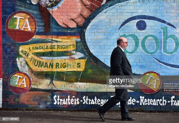 A man walks past a mural promoting Irish language rights on February 21 2018 in Belfast Northern Ireland Talks to restore the Northern Ireland power...
