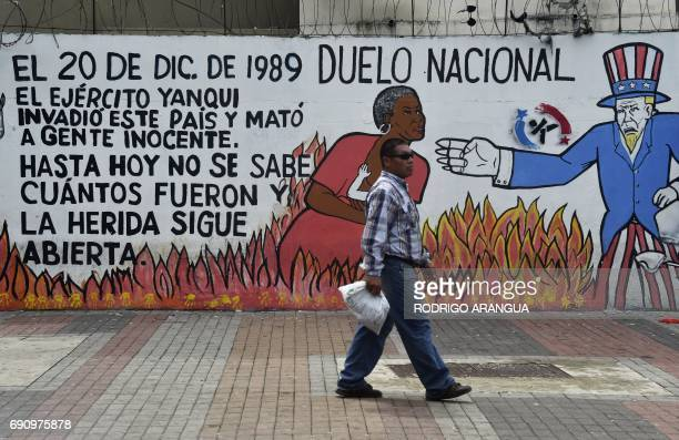 A man walks past a mural referring to the US invasion which ousted late former dictator Manuel Noriega who became Panama's de facto ruler in 1983 and...
