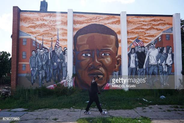 TOPSHOT A man walks past a mural with a portrait of Freddie Gray at North Mount and Presbury streets in the Sandtown neighborhood of west Baltimore...