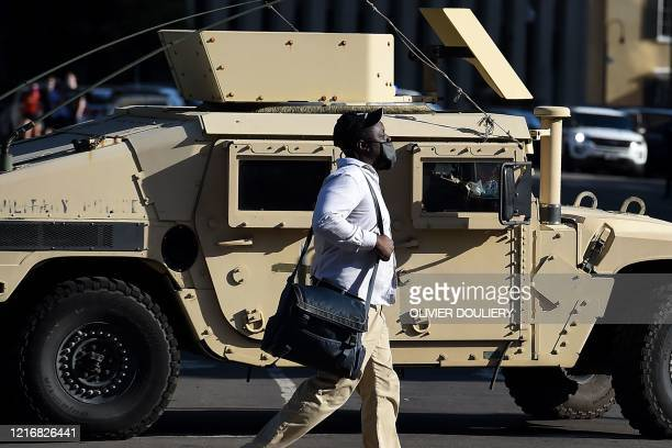A man walks past a National Guards armored vehicle near the White House as demonstrators gather to protest the killing of George Floyd on June 1 2020...