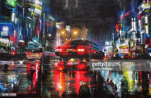 A man walks past a neon soaked street scene mural titled 'Belfast Blurry Eyed' by Dan Kitchener also known as DANK on March 1 2018 in Belfast...