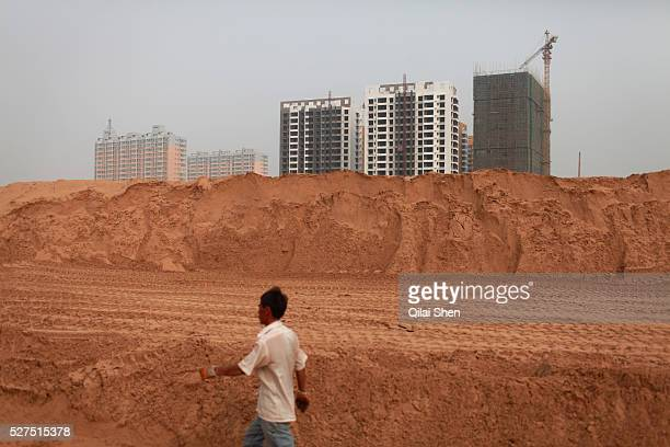 A man walks past a new apartment development on the outskirts of Yulin Shaanxi Province China on 14 August 2011 Like many coal rich regions in...