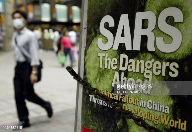 Man walks past a news headline on a newstand wearing mask to protect against SARS on a street in Hong Kong 06 May 2003. Six more people have died 06...