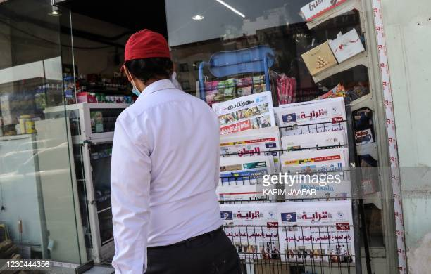 Man walks past a newspaper stand outside a shop in the Qatari capital Doha showing headlines about the summit of the six-nation Gulf Cooperation...