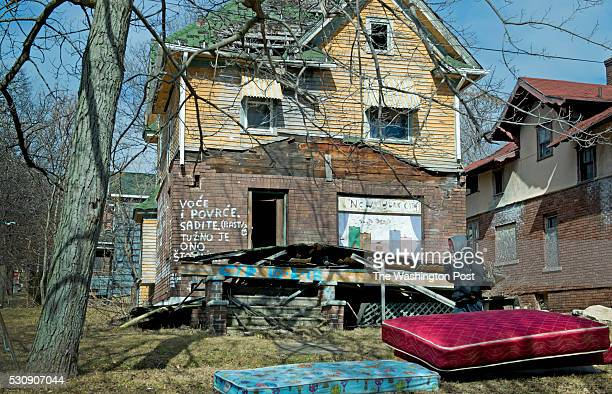 A man walks past a pair of abandoned homes near downtown Flint MI on February 29 2016 Flint has been in steady decline economically over the years...