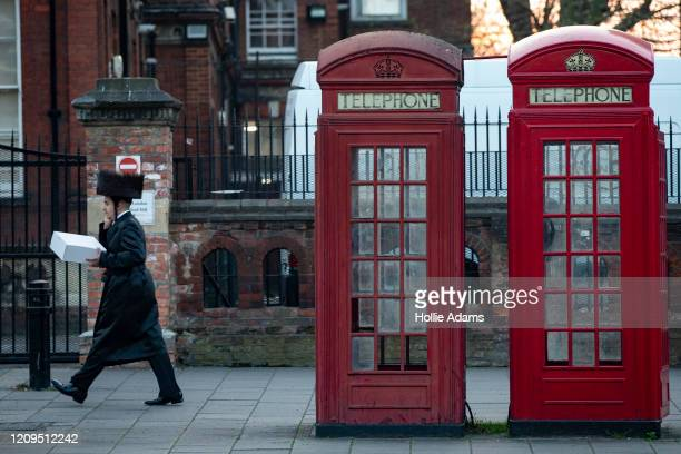 A man walks past a pair of telephone boxes in Stamford Hill on the evening of the Jewish holiday of Passover on April 8 2020 in London England The...
