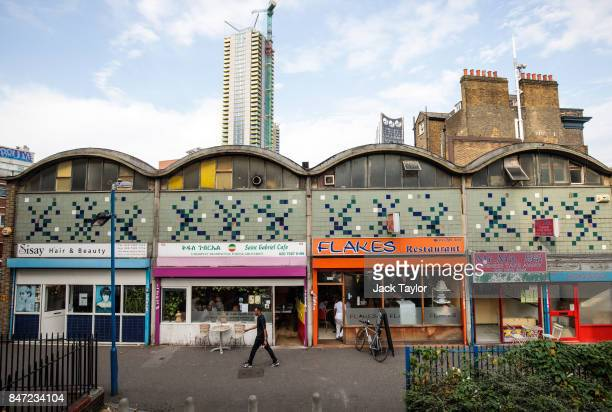 A man walks past a parade of shops and restaurants which sit in front of a housing development underway in Elephant and Castle on August 22 2017 in...