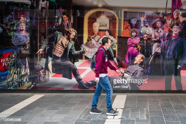 Man walks past a photo display outside the temporarily closed Sondheim theatre on July 02, 2020 in London, United Kingdom. The British government...