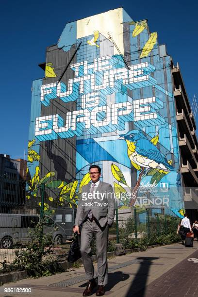 A man walks past a piece of street art by Belgian artist Julien Crevaels aka Novadead on the first day of the European Council leaders' summit on...