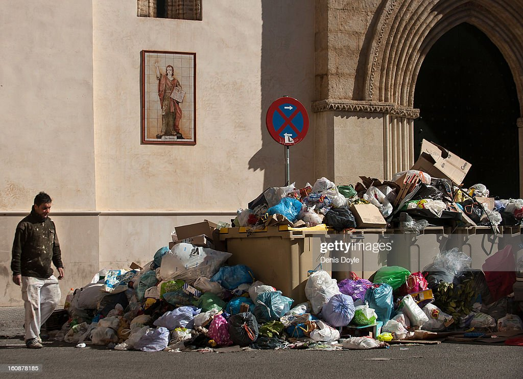 A man walks past a pile of uncollected grabage during the 11th day of the waste disposal strike on February 7, 2013 in Seville, Spain. Waste disposal workers are striking over a 5% proposed cut in their salary and an extended working week to 37.5 hours.